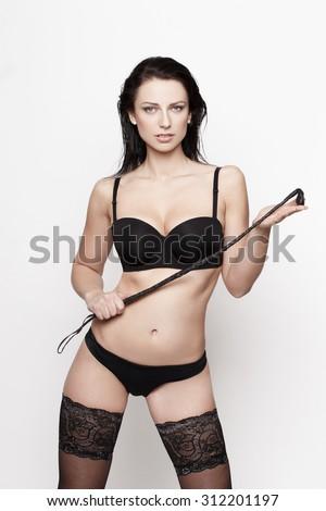 Sexy brunette woman in black underwear holding whip, bdsm - stock photo