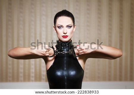 Sexy brunette woman in latex catsuit holding handcuffs, bdsm - stock photo
