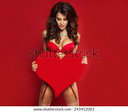 Sexy brunette woman in red lingerie holding big heart. St. Valentine's day. - stock photo