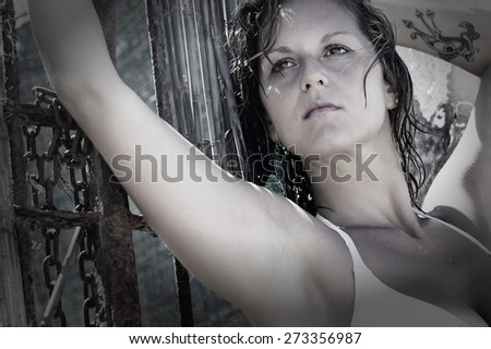Sexy brunette woman in white bikini posing outdoors against steel gate with chains. horizontal monochrome - stock photo