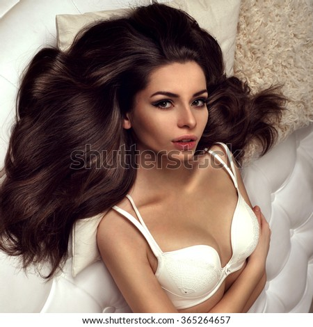 Sexy brunette woman lying on bed in elegant lingerie, looking at camera. Girl with perfect body relaxing. - stock photo