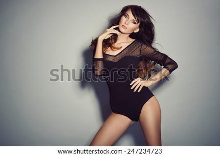 Sexy brunette woman posing in black bodysuit - stock photo
