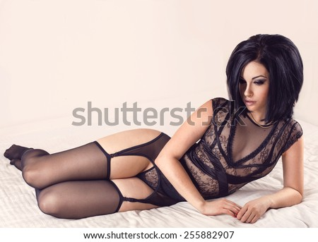 Sexy brunette woman posing laying on the bed in black lingerie and stockings on bright background with copyspace - stock photo