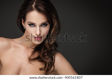 Sexy brunette woman posing on dark background - stock photo