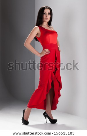 Sexy brunette woman wearing high heels and red dress - stock photo
