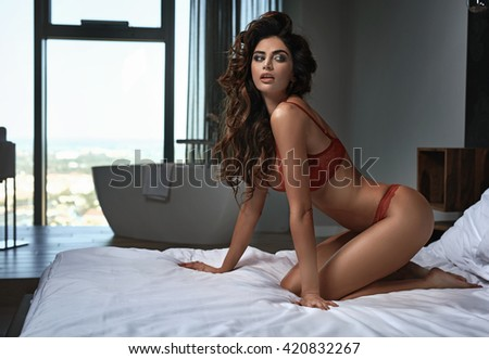 Sexy brunette young woman wearing red lingerie - stock photo