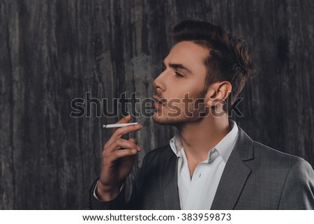 Sexy brutal man in gray suit smoking a cigarette - stock photo