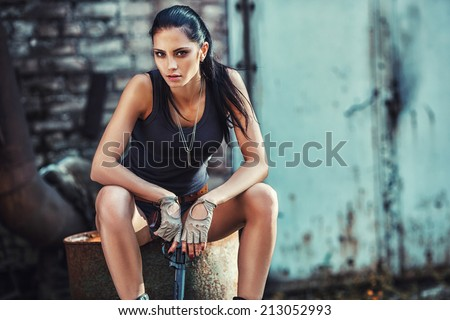 sexy brutal woman sitting in factory ruins and holding handgun - stock photo