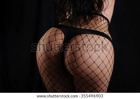 Sexy buttocks of a woman wearing black fishnet body stocking, black background. - stock photo