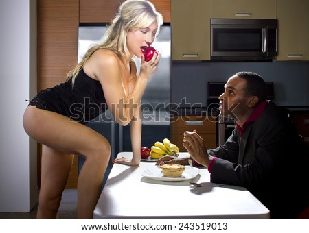 sexy caucasian female distracting african american boyfriend from dinner - stock photo