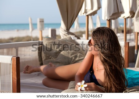 Sexy cheerful woman relaxing at the luxury beach. Girl at travel spa resort. Summer luxury vacation. - stock photo