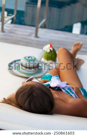 Sexy cheerful woman relaxing at the luxury poolside. Girl at travel spa resort pool in Hawaii island. Summer luxury vacation. (focus on woman head) - stock photo