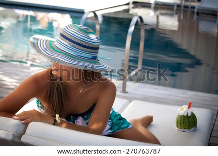 Sexy cheerful woman, relaxing at the luxury poolside. Girl at travel spa resort pool. Summer luxury vacation. - stock photo