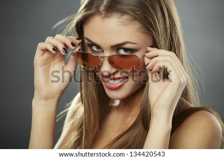 Sexy chic young woman looking at you over her sunglasses against grey background. - stock photo