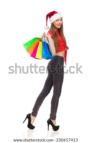 Sexy christmas girl holding colorful shopping bags and looking over shoulder. Full length studio shot isolated on white. - stock photo