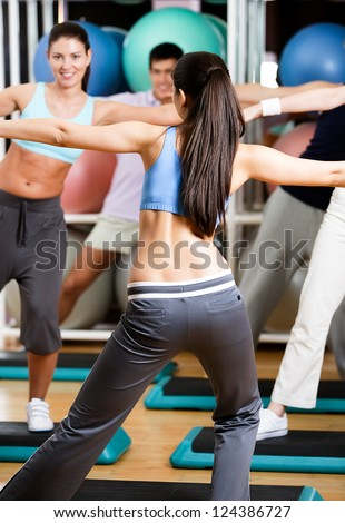 Sexy coach exercises with her group at the gym in a body shaping class - stock photo