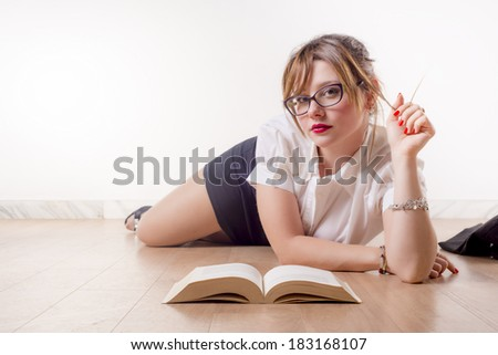 Sexy college girl reading a book on the floor - stock photo