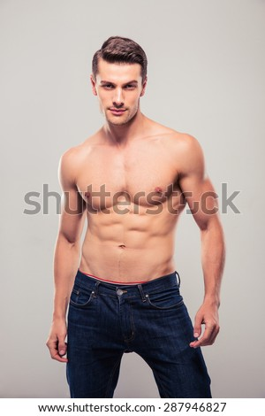 Sexy confident man posing over gray background and looking at camera - stock photo
