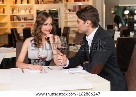 Sexy couple at the romantic dinner. Looking at each other drinking wine  - stock photo