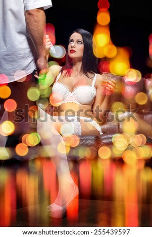 Sexy couple behind glass, sensual woman in underwear pulling mans tie, seduction, with night bokeh lights - stock photo