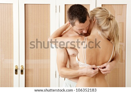 Sexy couple hugging and kissing in bedroom. Man undressing woman. - stock photo