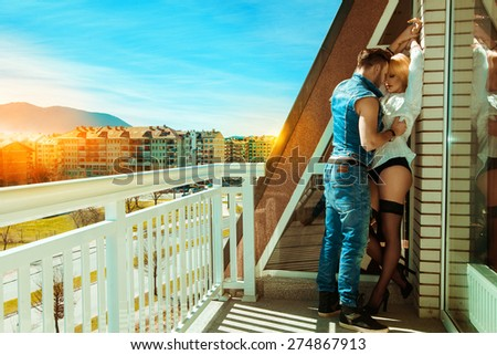 Sexy couple kissing each others on balcony. Summer time - stock photo