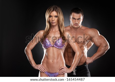 Sexy couple of fit man and woman showing muscular.  Bodybuilder standing together isolated over black background  - stock photo