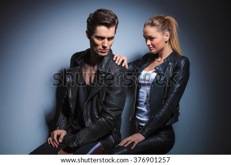 sexy couple posing in studio background seated. the man looks away while the woman is starring at him and touches his shoulder from behind - stock photo