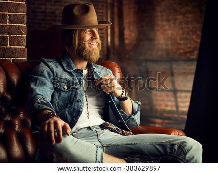 Sexy cowboy in a hat on the wall backround - stock photo