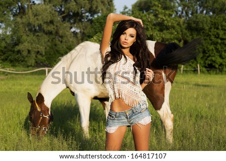 Sexy cowgirl posing at summer day with beautiful horse. Woman looking at camera. - stock photo