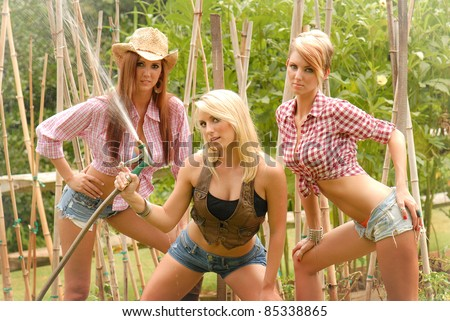 Sexy Cowgirls having fun with a water hose - stock photo