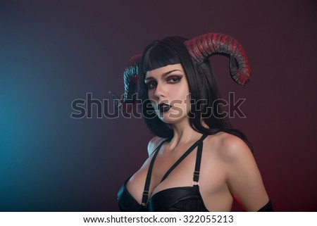 Sexy demon girl with red horns, studio shot for Halloween   - stock photo