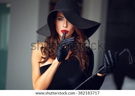 Sexy dominant woman in hat and whip showing no talk, bdsm - stock photo