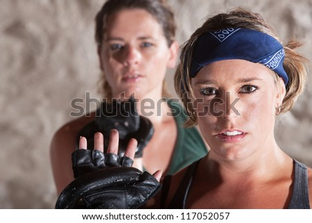 Sexy duo of women holding kettle bell weights - stock photo
