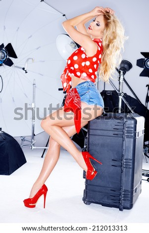 Sexy elegant model in trendy skimpy denim shorts  a red polka dot top and stilettos posing during a studio photo shoot with equipment - stock photo