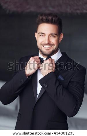 Sexy elegant young caucasian macho man tie a bow - stock photo