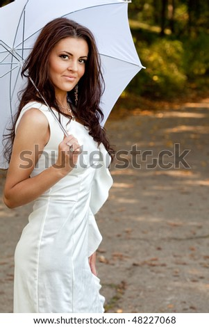 Sexy elegant young woman with umbrella outdoor - stock photo