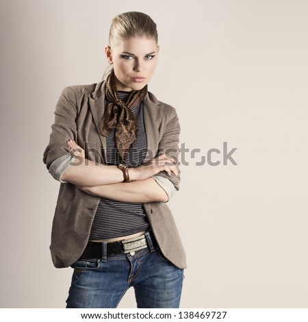 Sexy fashion girl. Beautiful young stylish model with professional makeup wearing jeans and jacket, looking at the camera. - stock photo
