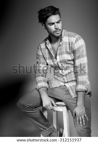 sexy fashion male model dressed casual posing against wall - stock photo