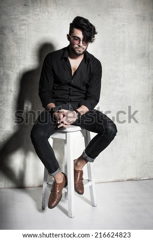 sexy fashion man model dressed casual posing dramatic against grunge wall - stock photo