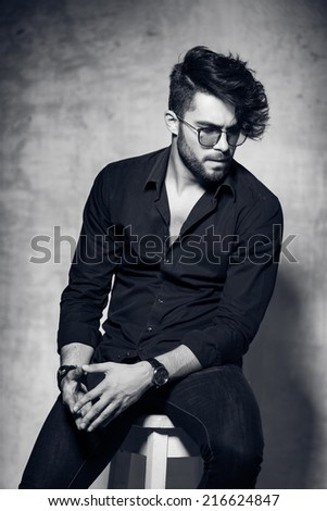 sexy fashion man model dressed casual wearing glasses posing dramatic against grunge wall - stock photo