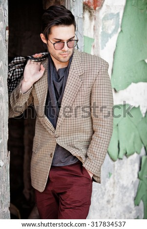 sexy fashion man model dressed vintage elegant holding a bag posing outdoor - stock photo