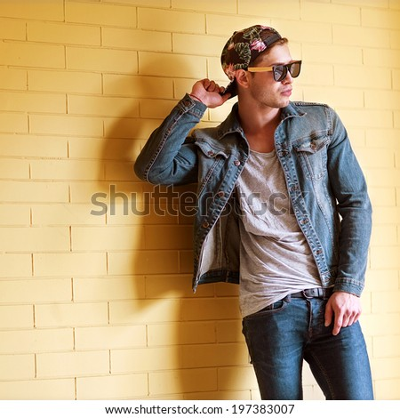 sexy fashion man with beard dressed casual smiling brick wall - stock photo