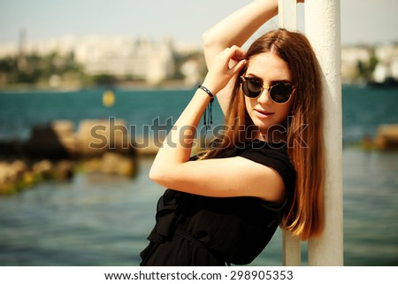 Sexy fashion portrait of young beautiful pretty girl posing outdoors near sea. Stylish woman walking in summer city.  - stock photo