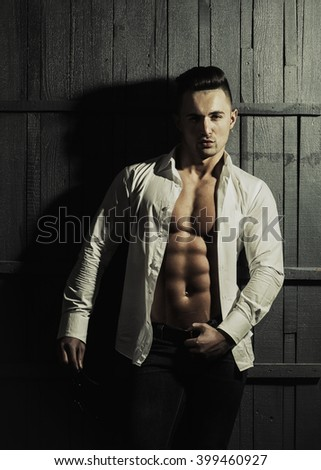 Sexy fashionable serious sensual muscular young macho man with bare torso in white shirt standing indoor on wooden background, vertical picture - stock photo