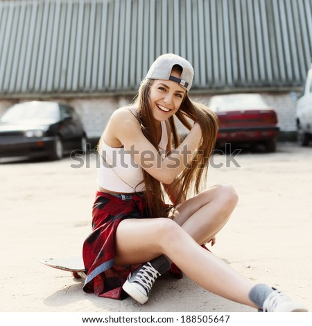 Sexy fashionable woman sitting on a skateboard laughs  - stock photo