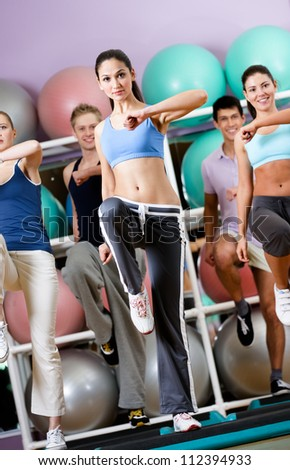 Sexy female coach exercises with her group on step boards at the gym in a sports class - stock photo