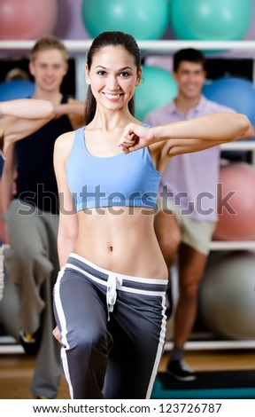 Sexy female coach works out with her group at the gym in a fitness class in order to keep fit - stock photo
