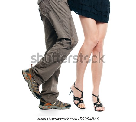 sexy female legs being assaulted by male legs, both isolated on white background - stock photo