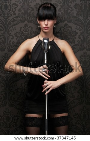 Sexy female singer wearing black dress holding a retro microphone over Damask wallpaper - stock photo